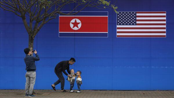 Cư dân Hà Nội tạo dáng trước hình ảnh lá cờ Bắc Triều Tiên và Mỹ trong những ngày diễn ra hội nghị thượng đỉnh Bắc Triều Tiên-Mỹ tại Hà Nội - Sputnik Việt Nam