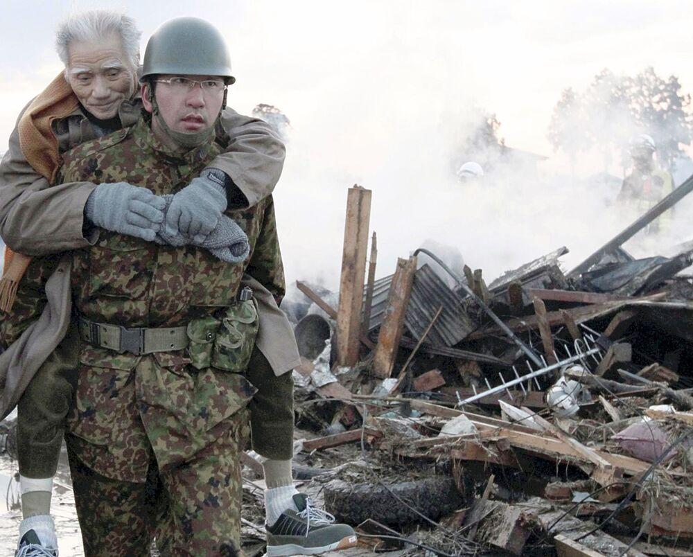 Quân nhân cõng trên mình người dân bị ảnh hưởng bởi trận động đất và sóng thần 2011 tại Nhật Bản