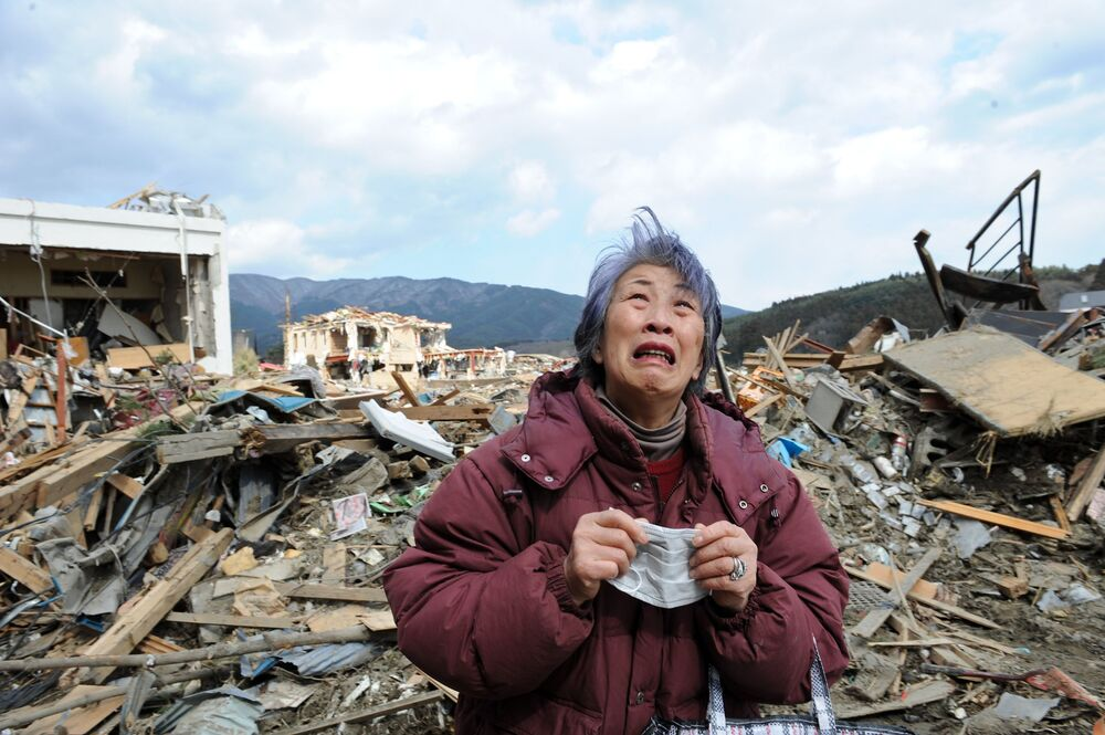 Người phụ nữ lớn tuổi khóc gần tòa nhà bị phá hủy của thành phố Rikudentakata, tám ngày sau trận động đất và sóng thần tấn công đất nước Nhật Bản ngày 11 tháng 3 năm 2011.