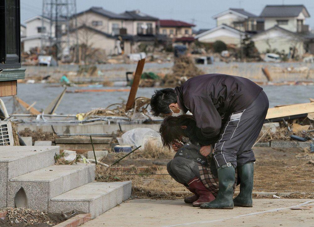 Người dân tại ngôi nhà bị phá hủy của họ ở thành phố Watari sau trận động đất và sóng thần tấn công đất nước Nhật Bản ngày 11 tháng 3 năm 2011