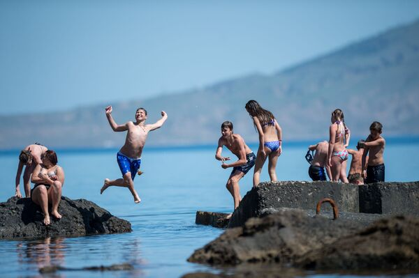 Du khách nhảy xuống nước từ đê chắn sóng ở Novyi Svet, Crưm - Sputnik Việt Nam
