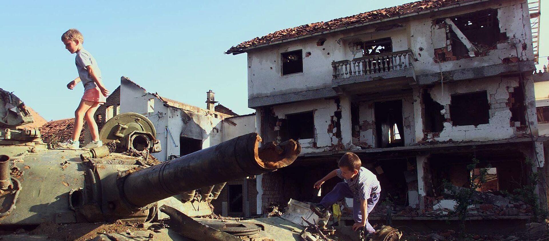 Trẻ em chơi trên chiếc xe tăng Serbia bị phá hủy trong vụ bắn phá của NATO tại thành phố Klina của Nam Tư, 1999 - Sputnik Việt Nam, 1920, 02.04.2019