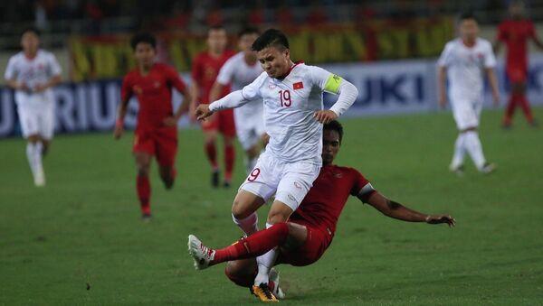 Quang Hải (số 19) nỗ lực đi bóng trong sự truy cản quyết liệt của hậu vệ U23 Indonesia. - Sputnik Việt Nam