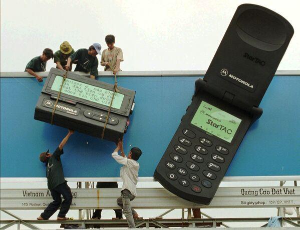Công nhân lắp đặt máy nhắn tin khổng lồ bên cạnh chiếc điện thoại di động khổng lồ với quảng cáo sản phẩm viễn thông của hãng Motorola tại Thành phố Hồ Chí Minh, năm 1996 - Sputnik Việt Nam