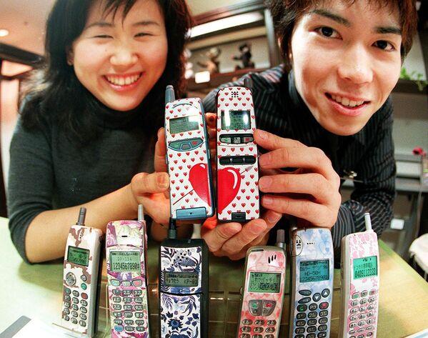 Cặp vợ chồng trẻ Nhật Bản khoe điện thoại di động dán mác hàng hiệu tại cửa hàng bách hóa Toki - Sputnik Việt Nam
