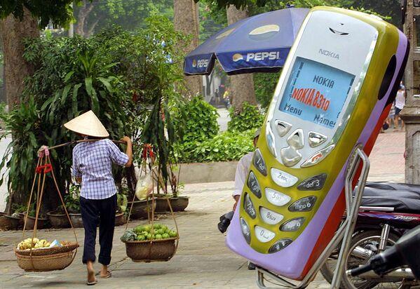 Người bán trái cây đi ngang qua cửa hàng điện thoại di động ở Hà Nội, Việt Nam. 2002 - Sputnik Việt Nam