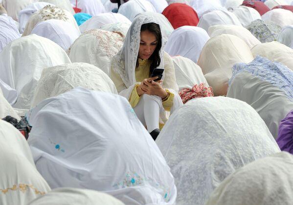 Người phụ nữ Hồi giáo với chiếc điện thoại di động giữa những người cầu nguyện trong lễ Eid al-Adha ở Jakarta - Sputnik Việt Nam