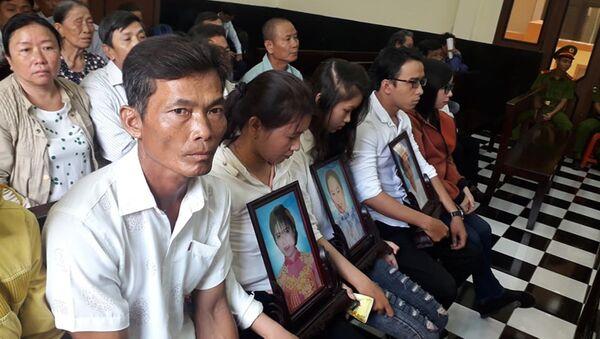 Người thân của các nạn nhân mang di ảnh đến dự phiên tòa.  - Sputnik Việt Nam