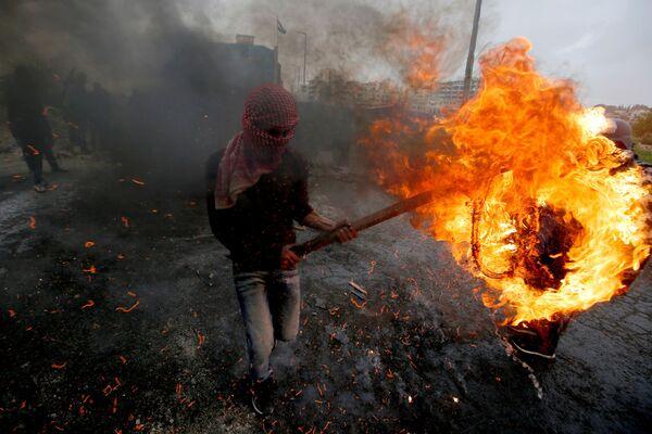 Một người Palestine đụng độ với lực lượng Israel gần khu định cư Do Thái Beit El ở Bờ Tây - Sputnik Việt Nam