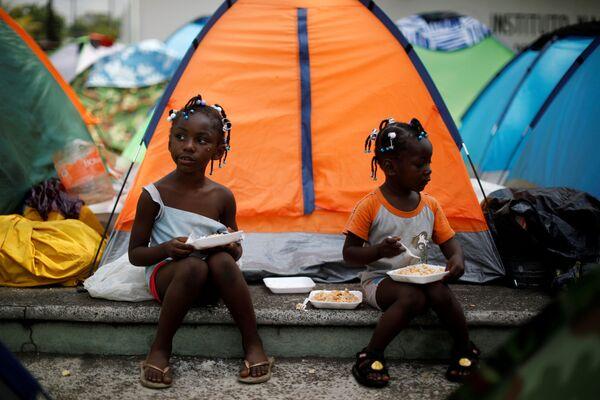 Hai cô bé Congo ngồi ăn bên lều trong trại ngẫu hứng gần Viện Di cư Quốc gia (INM) ở Tapachula, Mexico - Sputnik Việt Nam