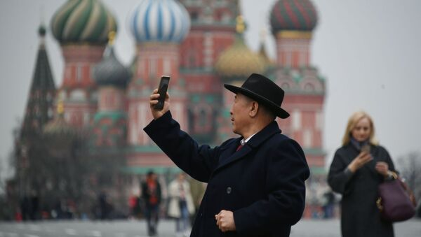 Турист фотографируется на Красной площади в Москве, на фоне храма Василия Блаженного - Sputnik Việt Nam