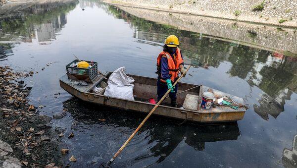 Các công nhân vệ sinh phải thường xuyên thu dọn rác thải trên bề mặt sông - Sputnik Việt Nam