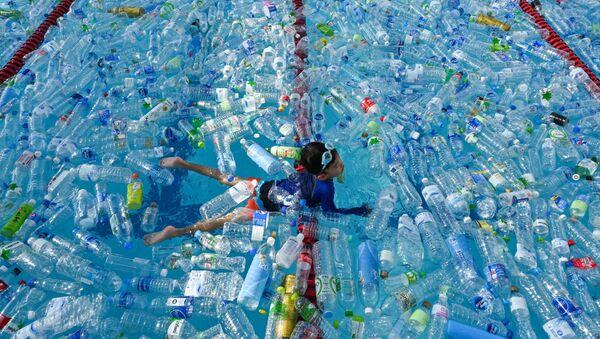 Đứa trẻ bơi trong bể chứa đầy chai nhựa trong chiến dịch thông tin về Ngày Đại dương thế giới ở Bangkok, Thái Lan - Sputnik Việt Nam