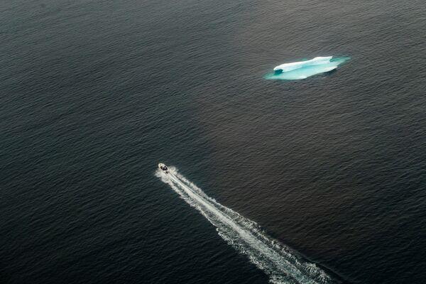 Một chiếc thuyền đi ngang qua tảng băng trôi trong đại dương gần Tasiilaq, Greenland - Sputnik Việt Nam
