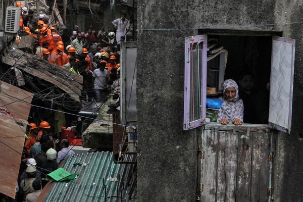 Một phụ nữ địa phương nhìn ra cửa sổ trong khi nhân viên cứu hộ tìm người sống sót sau vụ sập tòa nhà ở Mumbai, Ấn Độ - Sputnik Việt Nam
