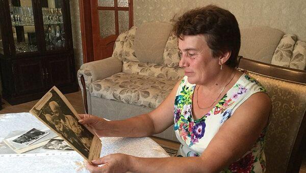 Cô ZalitaTarkil với bức ảnh thời thơ ấu, khi đó cô là bé gái được Chủ tịch Hồ Chí Minh bế trên tay  - Sputnik Việt Nam