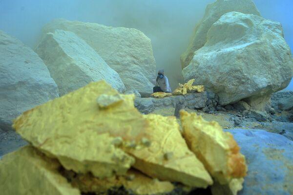 Thợ mỏ khuân vác túi lưu huỳnh từ mỏ đá trên núi lửa Kawah Ijen đang hoạt động ở Indonesia - Sputnik Việt Nam