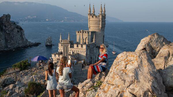 Отдыхающие фотографируются возле замка Ласточкино гнездо на береговой скале в поселке Гаспра в Крыму - Sputnik Việt Nam