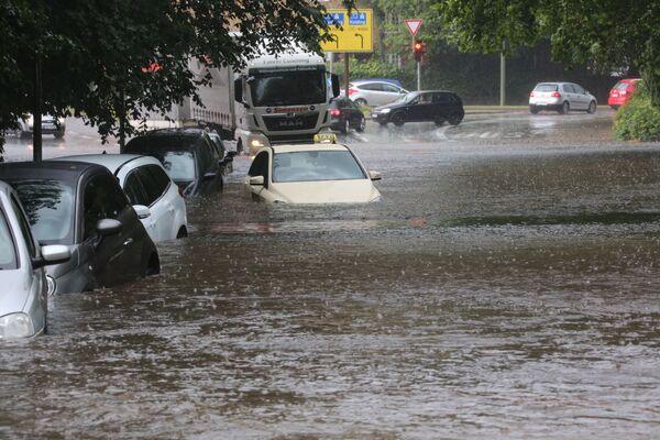 Xe ô tô trên đường phố ngập nước do mưa lớn ở Flensburg, Đức - Sputnik Việt Nam