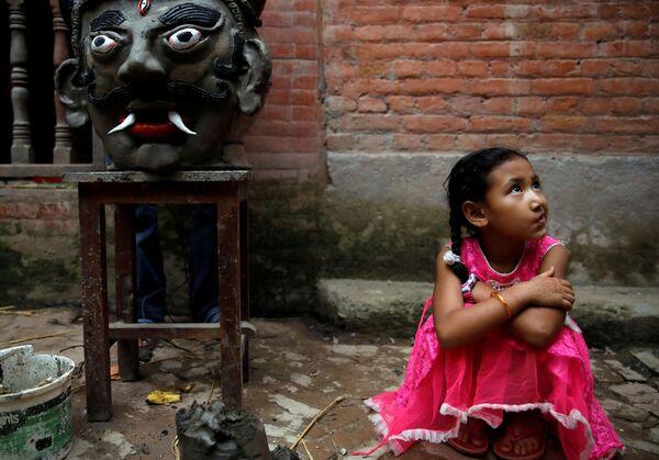 Cô bé ngồi cạnh đầu quỷ Ghantakarna trong lễ hội Ghantakarna, Nepal - Sputnik Việt Nam