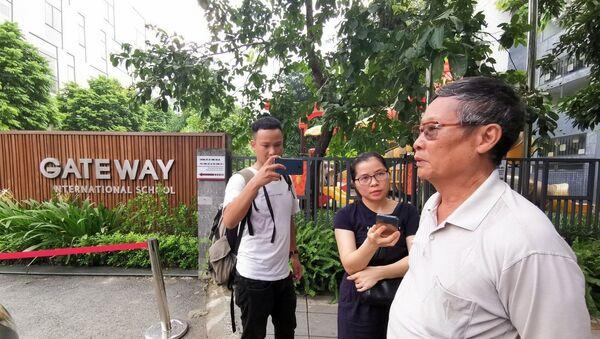 Phóng viên phỏng vấn người dân tại cổng trường Quốc tế Gateway.  - Sputnik Việt Nam