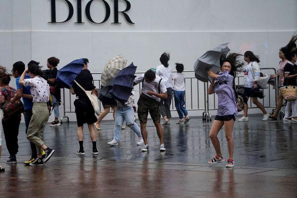 Cơn gió giật chiếc ô ra khỏi tay người dân thành phố Thượng Hải khi cơn bão Lekim tràn về  - Sputnik Việt Nam