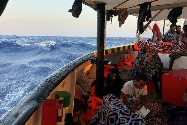 Người di cư đọc kinh Cô-ran trên tàu cứu hộ Tây Ban Nha Open Arms ở biển Địa Trung Hải - Sputnik Việt Nam