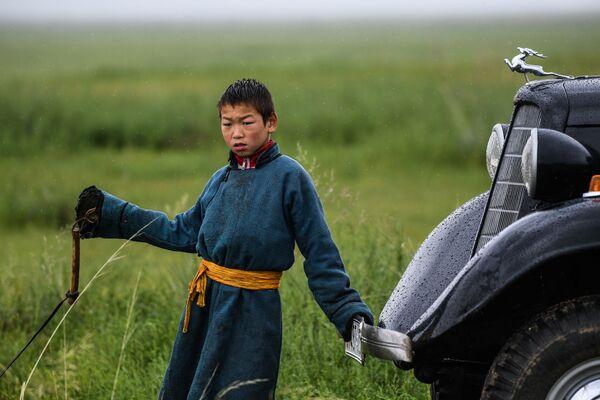 Một cậu bé bên cạnh chiếc xe GAZ-M1 trên cánh đồng ở quận Omnodelger thuộc tỉnh Khentii, Mông Cổ - Sputnik Việt Nam