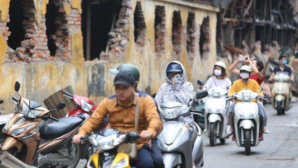 Người dân sinh sống tại đây phải đeo khẩu trang mỗi khi đi qua khu vực cháy nhà máy Bóng đèn Phích nước Rạng Đông. - Sputnik Việt Nam