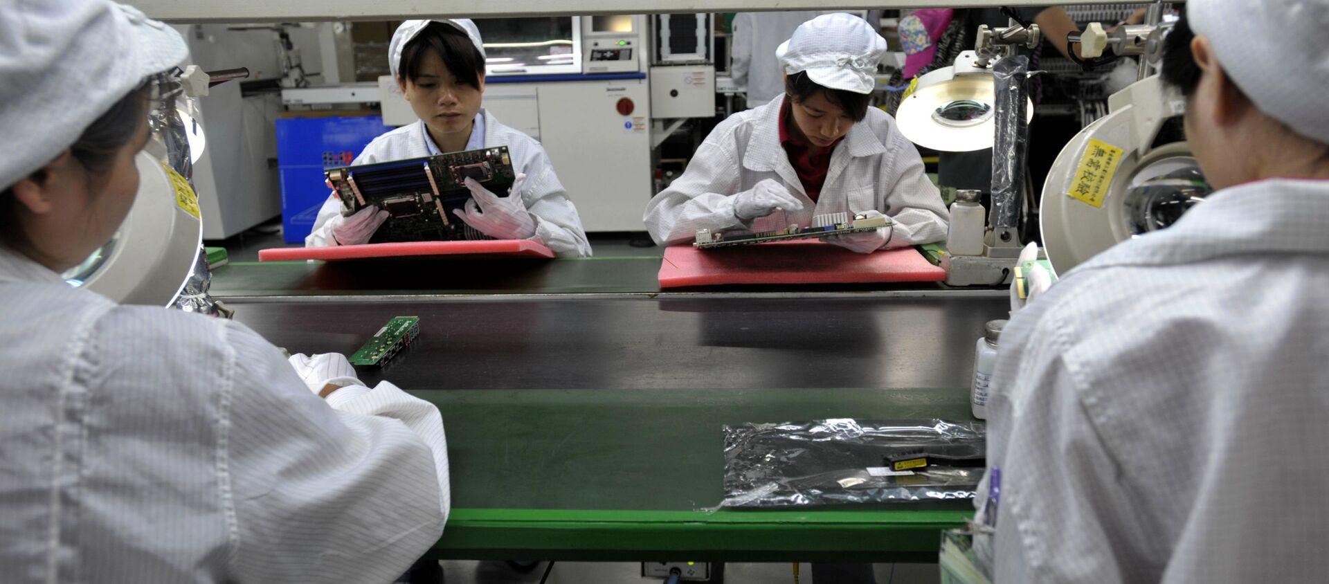 Công nhân Trung Quốc lắp ráp linh kiện điện tử trong nhà máy thuộc công ty khổng lồ Foxconn của Đài Loan tại Thâm Quyến, Trung Quốc - Sputnik Việt Nam, 1920, 26.11.2020