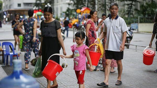 Hình ảnh người dân KĐT Linh Đàm (Hoàng Mai, Hà Nội) rồng rắn xách xô chậu đi lấy nước sạch từ tét nước dịch vụ đã đang diễn ra trong gần một tuần nay. - Sputnik Việt Nam