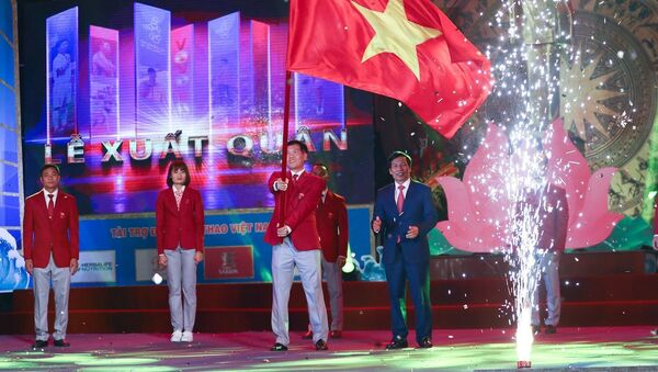 Ông Trần Đức Phấn, Phó Tổng cục trưởng Tổng cục Thể dục thể thao, Trưởng Đoàn thể thao Việt Nam tham dự SEA Games 30 phất cao lá quốc kỳ Việt Nam trong Lễ xuất quân - Sputnik Việt Nam