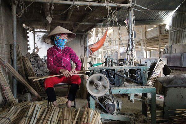 Công nhân dùng máy cắt những thanh tre thành những thanh nhỏ chuẩn bị làm tăm hương   - Sputnik Việt Nam