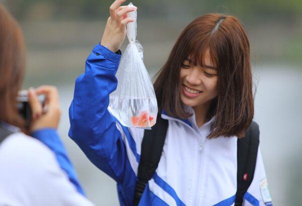 Các bạn trẻ hào hứng với phong tục thả cá chép để tiễn đưa ông Táo về trời. - Sputnik Việt Nam