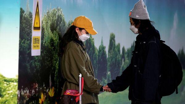 Cặp đôi đeo khẩu trang ở sân bay Phố Đông (Thượng Hải) - Sputnik Việt Nam