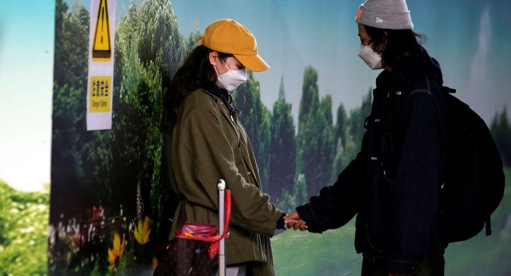 Cặp đôi đeo khẩu trang ở sân bay Phố Đông (Thượng Hải)