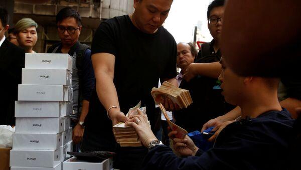 Một người đàn ông cầm một đống tiền giấy để mua một chiếc iPhone X mới mà những người vừa mua nó tại một cửa hàng Apple đang bán lại nó trên một con phố ở Hồng Kông, Trung Quốc. - Sputnik Việt Nam