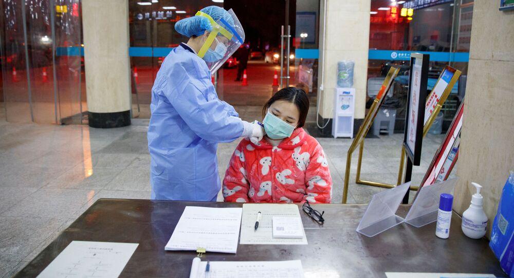Một y tá đo nhiệt độ bệnh nhân trong bệnh viện ở quận Yueyang, tỉnh Hồ Nam, Trung Quốc