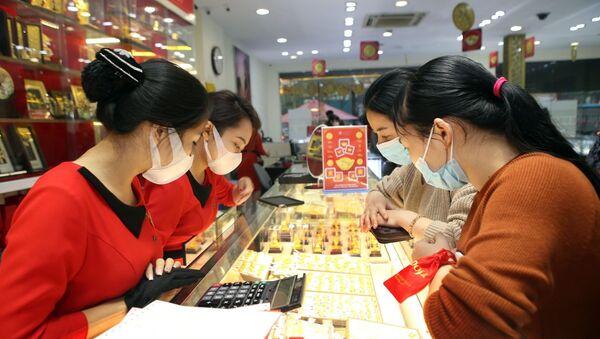 Người dân và nhân viên đều đeo khẩu trang trong khi giao dịch tại Trung tâm vàng bạc trang sức DOJI, số 209 Xã Đàn (Hà Nội). - Sputnik Việt Nam