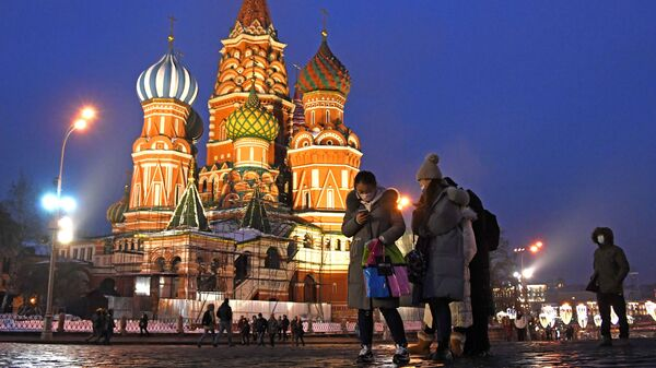 Khách du lịch nước ngoài đeo khẩu trang bảo vệ chụp ảnh gần Nhà thờ Thánh St. Basil trên Quảng trường Đỏ ở Moskva - Sputnik Việt Nam