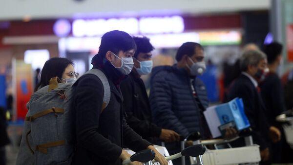 Hành khách trang bị khẩu trang kín mít khi đến sân bay quốc tế Nội Bài. - Sputnik Việt Nam