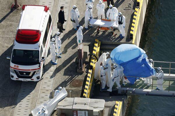 Các sĩ quan cảnh sát mặc đồ bảo hộ đưa hành khách bị bệnh trên tàu du lịch Diamond Princes lên xe cứu thương - Sputnik Việt Nam