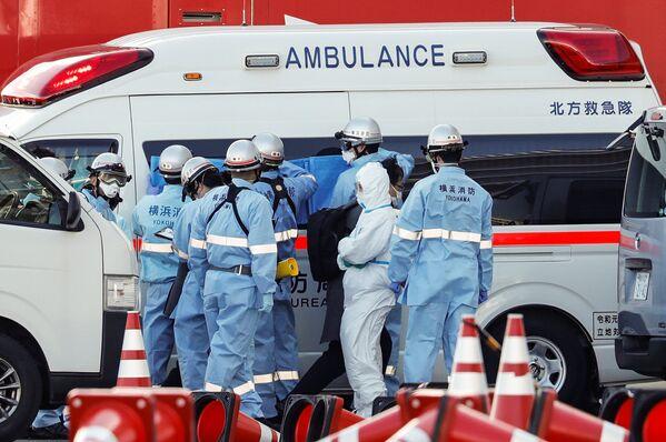 Lính cứu hỏa mặc đồ bảo hộ đưa hành khách bị bệnh trên tàu Diamond Princes lên xe cứu thương  - Sputnik Việt Nam