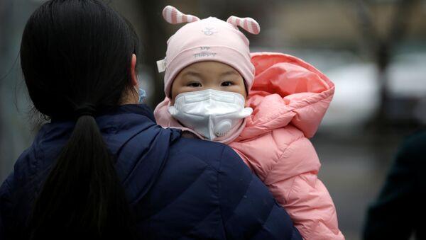 Một phụ nữ có con đeo mặt nạ y tế trên đường phố Bắc Kinh - Sputnik Việt Nam
