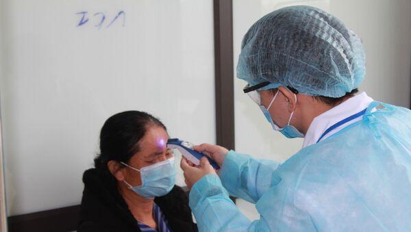 Kiểm tra thân nhiệt định kỳ cho các trường hợp nghi ngờ nhiễm COVID-19. - Sputnik Việt Nam