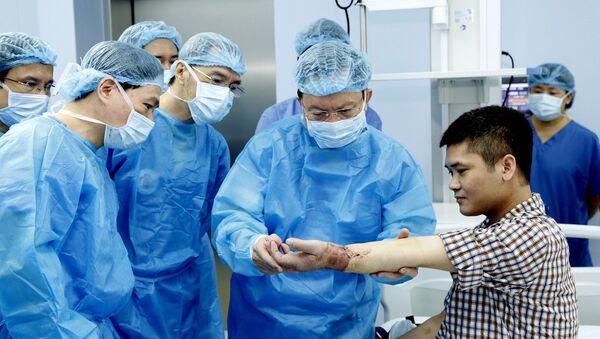 Trung tướng, GS,TS, Thầy thuốc nhân dân Mai Hồng Bàng, Giám đốc bệnh viện Trung ương Quân đội 108 kiểm tra chức năng vận động của bệnh nhân sau ca ghép - Sputnik Việt Nam