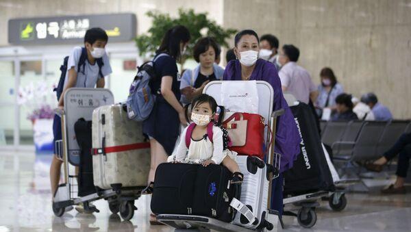 Пассажиры в защитных респираторных масках в аэропорту Гимпо в Сеуле  - Sputnik Việt Nam