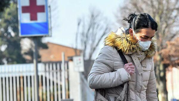 Một người phụ nữ đeo mặt nạ bảo vệ rời bệnh viện Codogno ở miền bắc Italy. - Sputnik Việt Nam