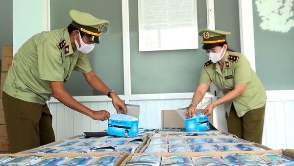 Lực lượng quản lý thị trường tỉnh An Giang kiểm tra số khẩu trang y tế xuất lậu vừa bị bắt giữ. - Sputnik Việt Nam