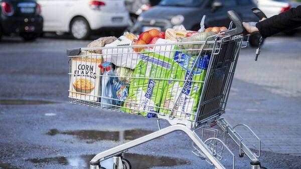 Khách hàng với chiếc xe đẩy chất đầy ắp thực phẩm ở siêu thị Đức - Sputnik Việt Nam